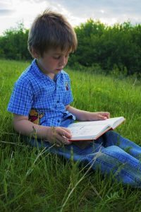 boy reading outdoors
