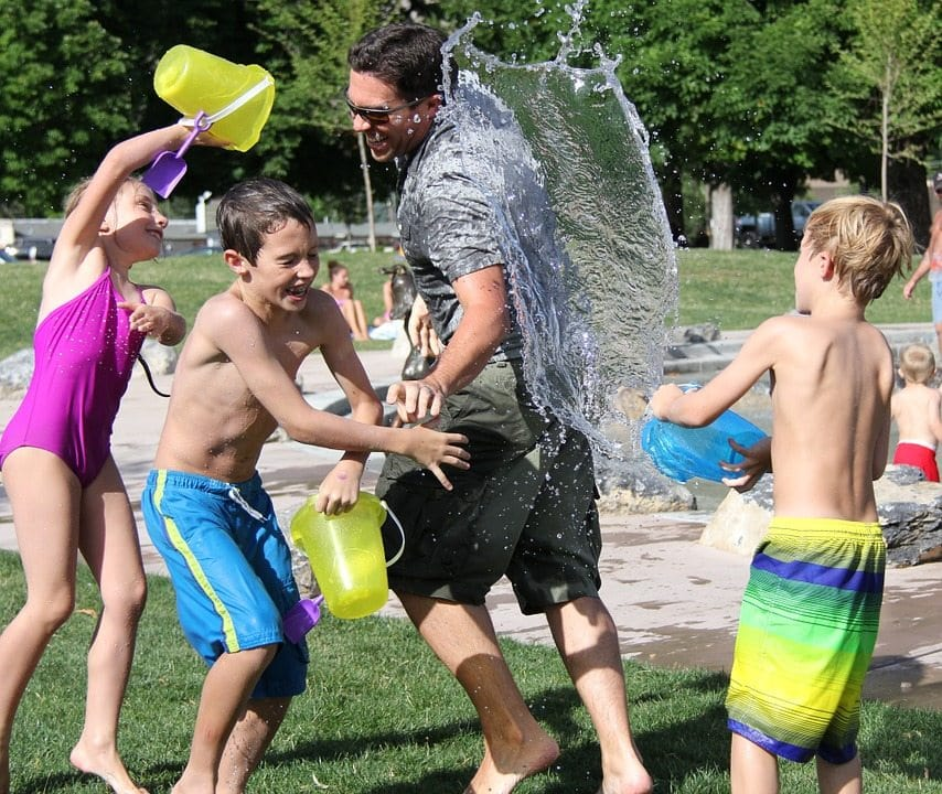kids and grownup having water fight