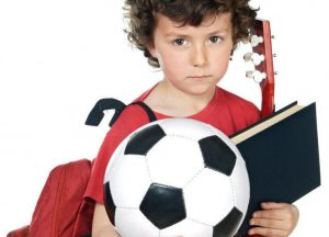 boy holding ball, book, backpack, guitar