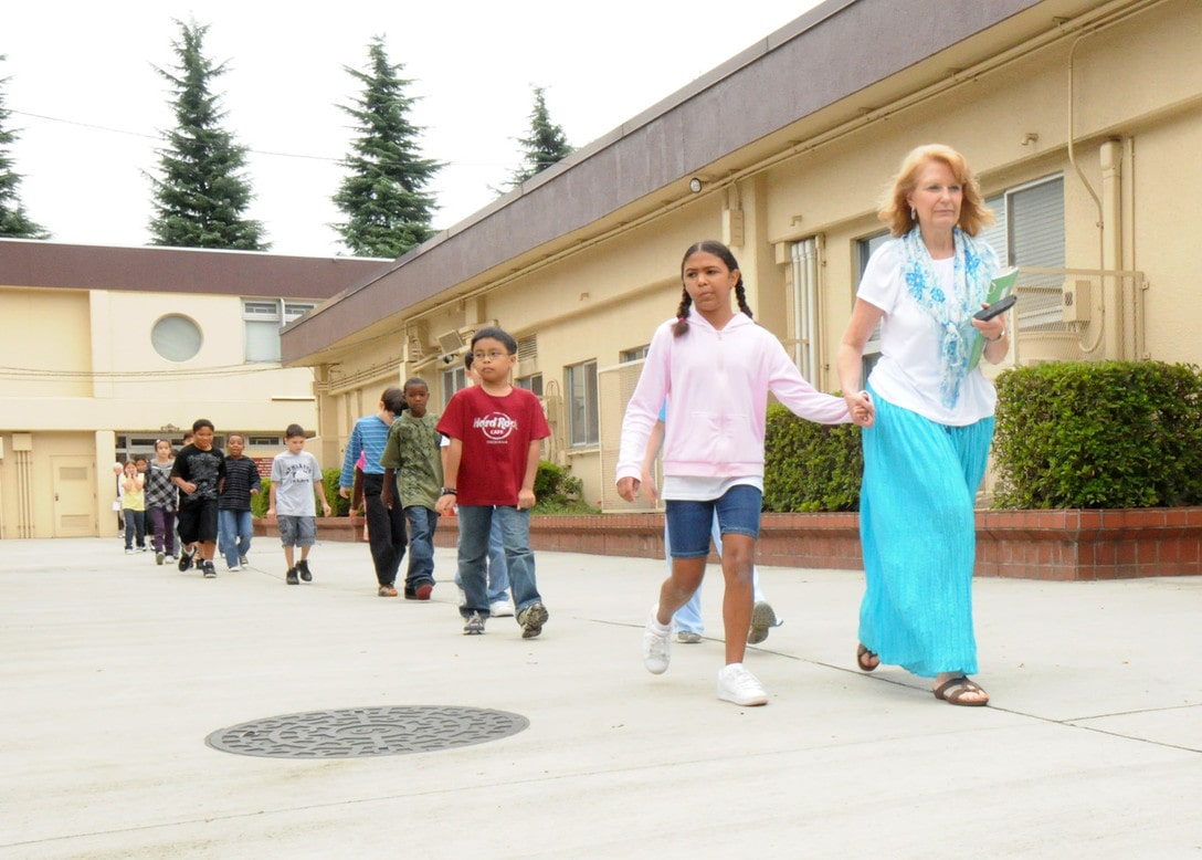 teacher leads students in fire drill