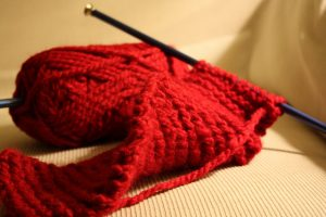 red yard and knitting needles