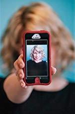 Doreen Dodgen-Magee holding smartphone displaying herself