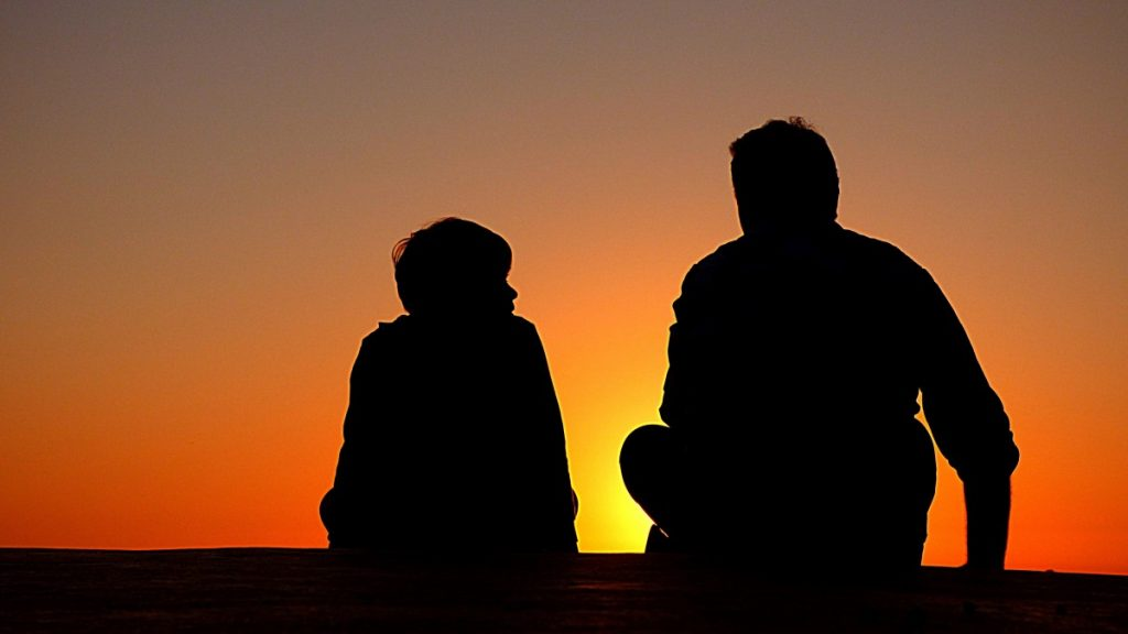man and boy talking in silhouette