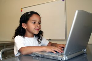 young girl sitting in front of laptop