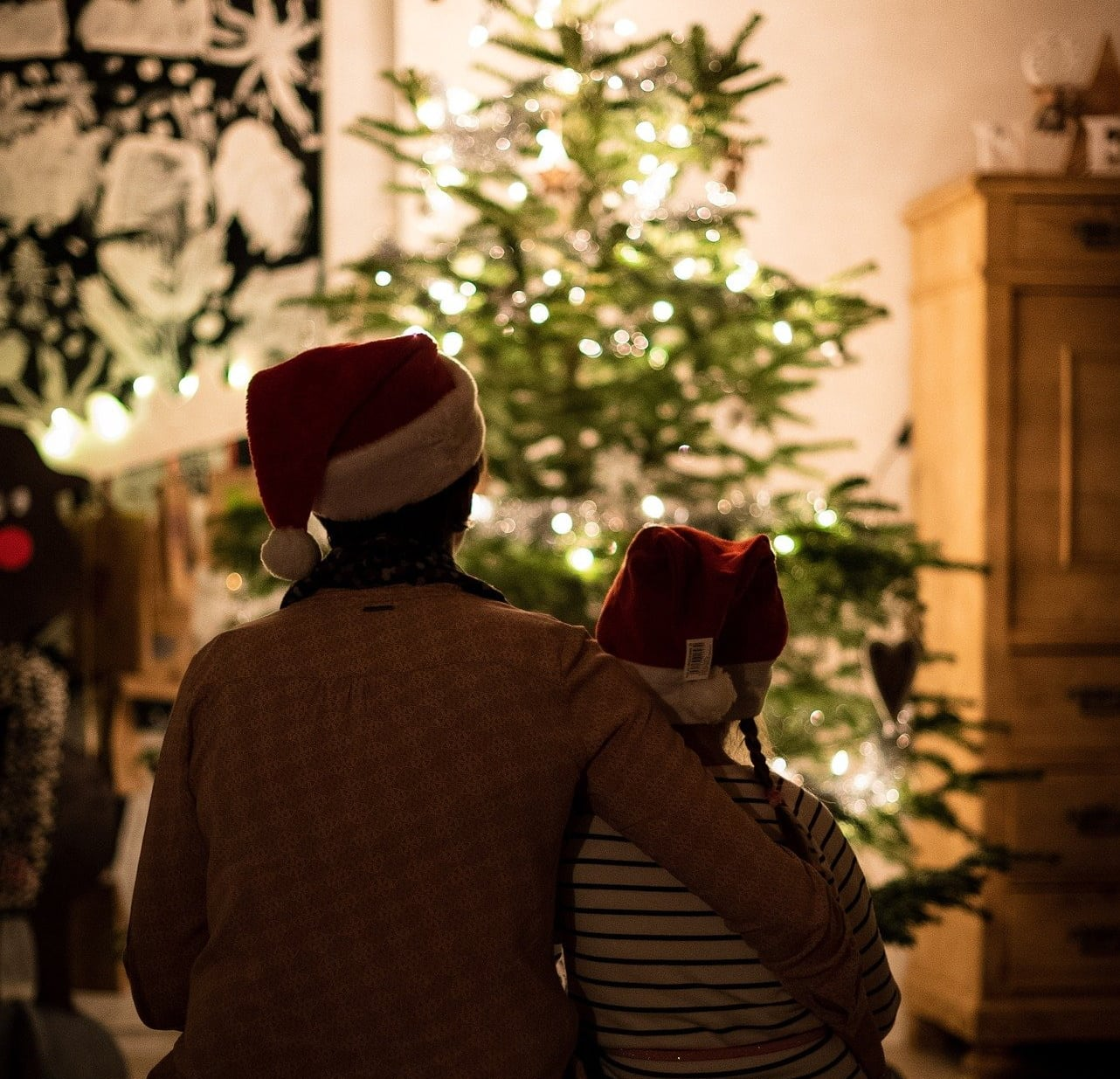 parent and child in front of Christmas tree