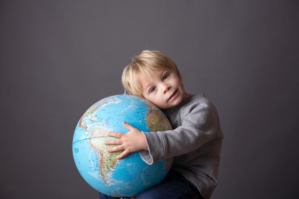 young boy hugging globe
