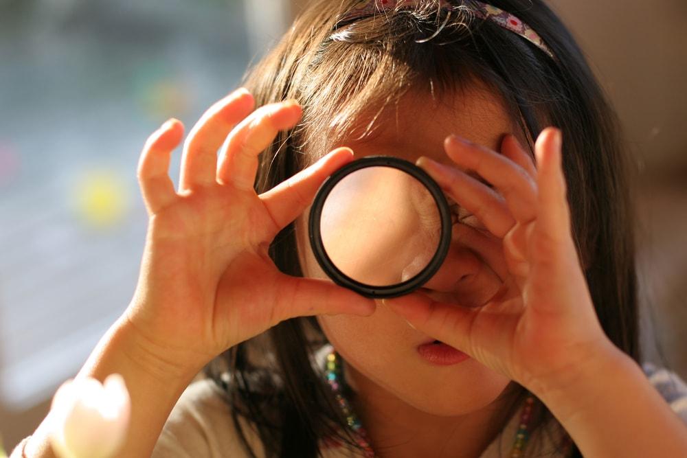 girl looking through photo lens