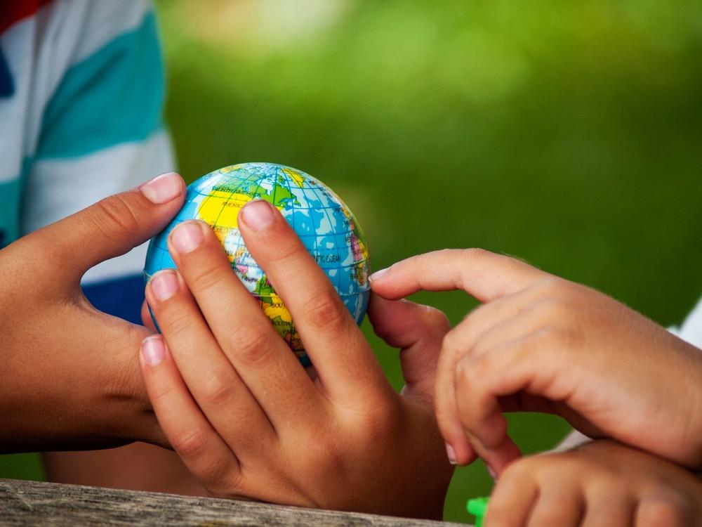 children's hands holding Earth model